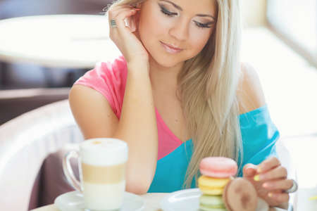 hot girl: portrait of a pretty young blonde woman sitting in a cafe in colorful bright t-short with a cup of coffee latte and macaroon cookies on the table Stock Photo