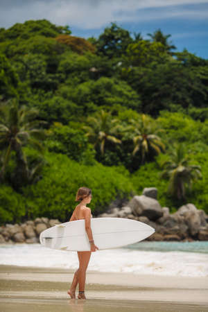 Surfing beach woman  Happy surfer girl running laughing cheerful having fun with bodyboarding surfboard on summer holidays vacation travel on Tropical ocean beach photo