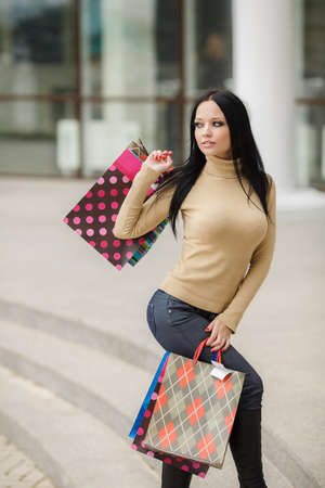 Beautiful shopping woman happy holding shopping bags outdoor  Walking in the street photo