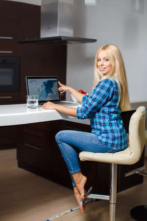 Smiling young woman sitting with laptop in modern kitchen photo