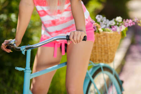 Beautiful woman s legs on Bicycle in Countryside, Summer Lifestyle photo