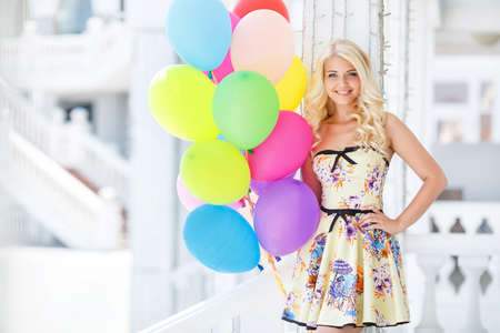 Pretty smiling woman in a summer dress, holding a bunch of colorful balloons in front of a building with columns photo