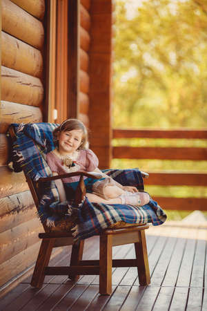 beautiful young girl portrait playing outdoors on wooden terrace photo
