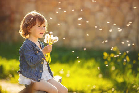 Portrait of a cute little girl in sunny summer day at green nature background photo