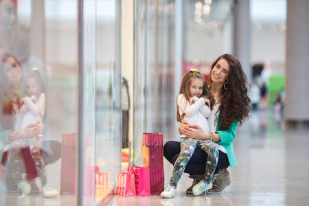 Young mother and her daughter doing shopping together in Shopping mall photo