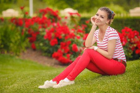 belle brunette: Portrait de la belle jeune femme brune vêtue lumineux t-courtes et pantalon rouges colorés, assis sur l'herbe au parc de verdure de l'été Banque d'images