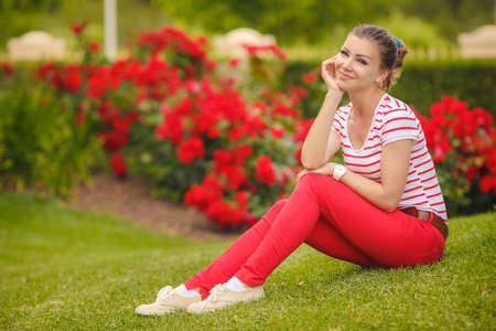 beautiful brunette: Portrait of young beautiful brunette woman wearing colourful bright t-short and red trousers, sitting on grass at summer green park