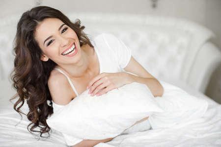 매력적인 미소 흰색 아늑한 침대 포용 베개에 누워 아름 다운 젊은 갈색 머리 여자 - 현대 침실에서 여자의 실내 초상화