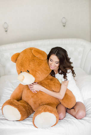 cosily: Pretty girl lying on the bed with a teddy bear Stock Photo