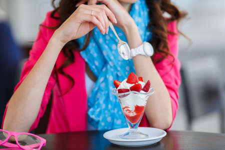 cote d'azure: Beautiful sexy brunette woman in restaurant cafe with ice cream cake alluring woman in bright clothes and hairstyle and makeup eating dessert  Beauty fashion Stock Photo