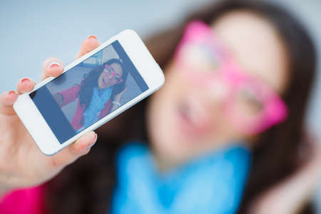 taking photograph: Beautiful young woman photographing herself with phone  Cute smiling young Caucasian teenage girl taking a selfie outdoors on sunny summer day