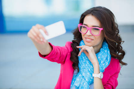 Beautiful young woman photographing herself with phone  Cute smiling young Caucasian teenage girl taking a selfie outdoors on sunny summer day