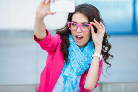 Mooie jonge vrouw die fotografeert met telefoon Cute lachende jonge blanke tiener meisje dat een Selfie buiten op zonnige zomerdag