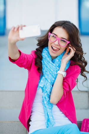 Beautiful young woman photographing herself with phone  Cute smiling young Caucasian teenage girl taking a selfie outdoors on sunny summer day  photo
