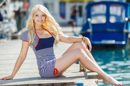 striped vest: Beautiful sexy blonde woman wearing sailor striped dress posing near boats