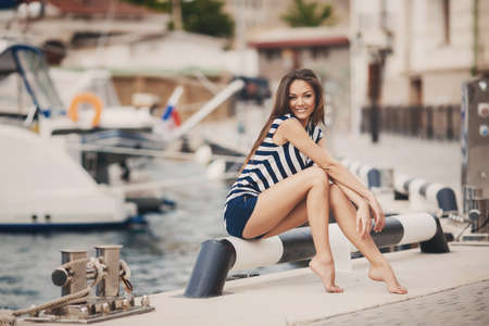 Beautiful woman sailing, young adult lady enjoying summer travel photo