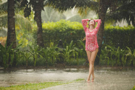 moody: Portrait of a beautiful happy woman enjoying tropical rain falling on her in an exotic garden  Stock Photo