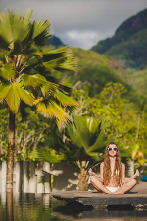 Spa vacation retreat woman relaxing at luxury travel resort  Happy blissful asian young woman in bikini in meditation enjoying summer sun and tanning during holidays on Hawaii  photo