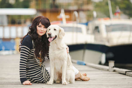 endear: Beautiful girl with her dog near sea  Portrait of young girl with her dog  Stock Photo