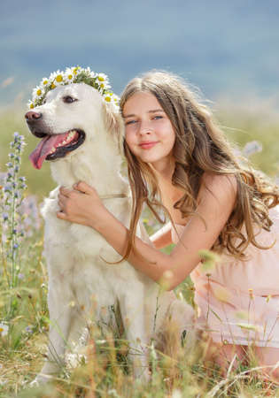Beautiful woman playing with her dog  Outdoor portrait  series  Woman embraces golden retriever lying on the green grass  Woman playing with her dog outdoors photo