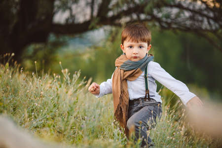 stylish baby boy having fun outside in the park  Cute happy boy child outdoors photo