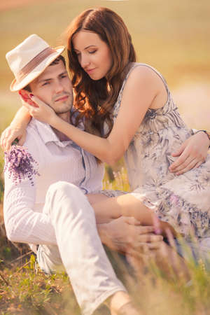 Young couple in love outdoor Stunning sensual outdoor portrait of young stylish fashion couple posing in summer in field photo