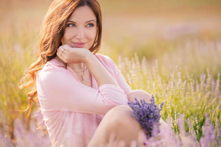 Beautiful girl on the lavender field  smiling beautiful brunette in the lavender field  Reklamní fotografie