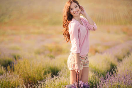 Beautiful girl on the lavender field  smiling beautiful brunette in the lavender field  Stock Photo