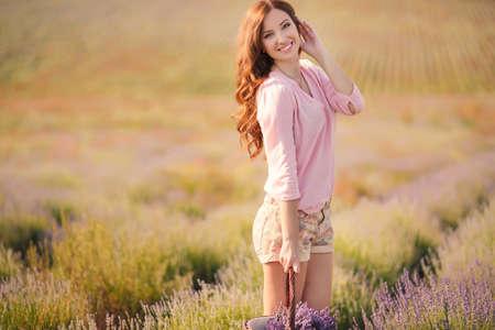 Belle fille sur le champ de lavande en souriant belle brune dans le champ de lavande
