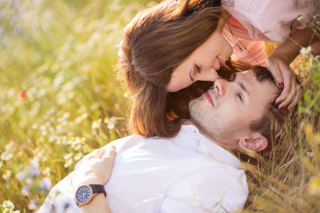 Young beautiful sensual couple outdoor kiss in windy weather in summer corn field  Young couple in love outdoor Stunning sensual outdoor portrait of young stylish fashion couple posing in summer field photo