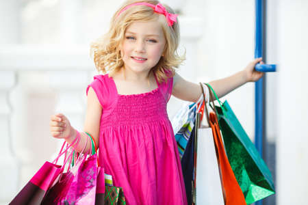 curios: Cheerful preschool girl walking with shopping bags  Pretty smiling little girl with shopping bags with thumb up sign in the shop
