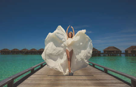 jumping bride in wedding dress and having fun on tropical island of maldives photo
