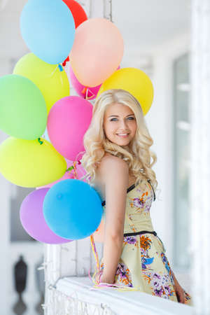 summer holidays, celebration and lifestyle concept - beautiful blonde woman with colorful balloons in the city  Bright summer portrait photo