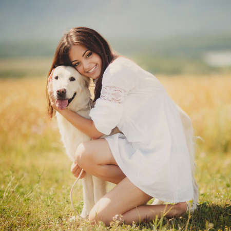 Beautiful woman plays with the dog on the nature  Outdoor portrait  Series  Young woman with dog Outdoor portrait day photo