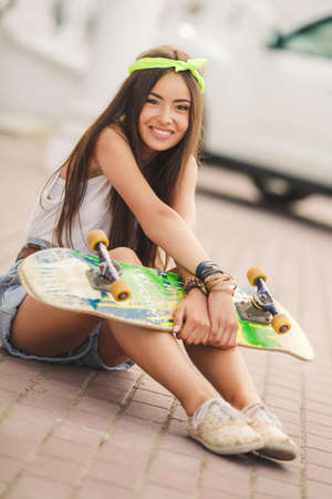 Sunny fashion outdoor urban portrait of pretty brunette fashion woman in city  Beautiful hipster girl with skate board wearing sunglasses  Beautiful and fashion young woman posing with a skateboard photo