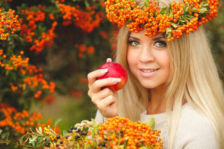 Beautiful woman in Orange wreath with Red Apple in hand  Portrait of a beautiful young woman, walk in the fresh air in the autumn photo