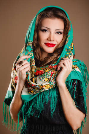portrait of a beautiful young woman with a scarf on her head  Russian beauty  Russian national traditional scarf on head  photo