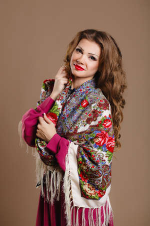 beautiful oriental look  portrait of a beautiful young woman with a scarf  Russian beauty  Russian national traditional scarf photo