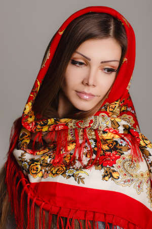 beautiful oriental look  portrait of a beautiful young woman with a scarf on her head  Russian beauty  Russian national traditional scarf on head  photo