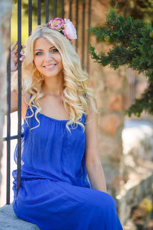 Summer portrait of a beautiful young blond Caucasian girl with straight hair in blue dress outdoors in the Park photo