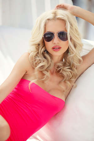 sexy blonde fashionable Woman luxury living lifestyle lying on sofa outside smiling confident at camera  Beautiful multicultural young elegant woman in white dress outdoors  photo