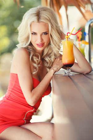 beautiful sexy blonde Woman in bar on Hawaii at beach club at sunset  Beautiful girl enjoying alcoholic beverage cocktail outside  Smiling happy Caucasian blonde woman on Hawaiian beach  photo