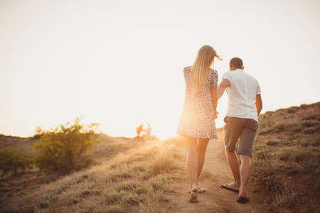 Young couple in love, an attractive man and woman enjoying a romantic evening, holding hands to watch the sunset