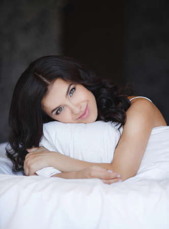 Portrait of young woman lying at the bed at early morning  Beautiful young woman with attractive smile sitting embracing pillow - indoors  Portrait of a pretty woman relaxing in bed photo