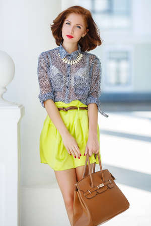 Beautiful brunette young woman wearing dress and walking on the street photo