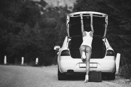 legs open: Woman with head getting into the opened car trunk
