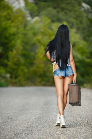 country girls: Young woman hiker walking with suitcase in hand