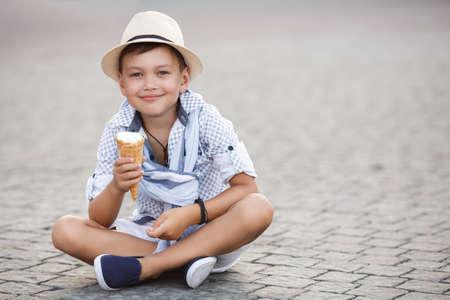 kid eating ice cream ioutdoor. happy child boy eating ice cream photo