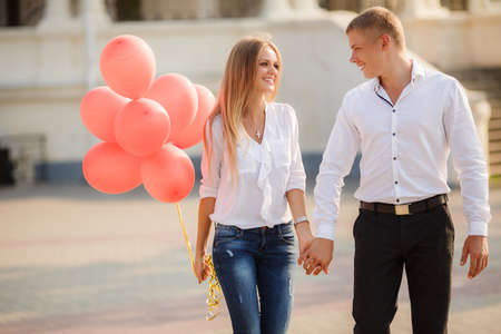 summer holidays, celebration and dating concept - couple with colorful balloons in the city. Young couple kissing among white columns and holding bunch of balloons photo