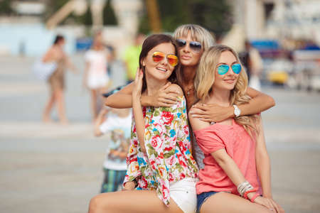 Three beautiful girlfriends with with Shopping Bags. Three beautiful young woman sitting on bench in the city photo